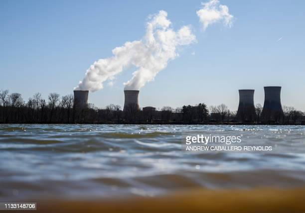 Steam rises out of the nuclear plant on Three Mile Island with the operational plant run by Exelon Generation in Middletown Pennsylvania on March 26...