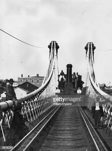 A steam train approaches along the Railway Suspension Bridge over the Niagara River built in 1855 by John A Roebling to carry the Grand Trunk Railway...