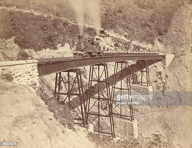 A steam train crossing a bridge in Mexico The passengers are travelling in open trucks