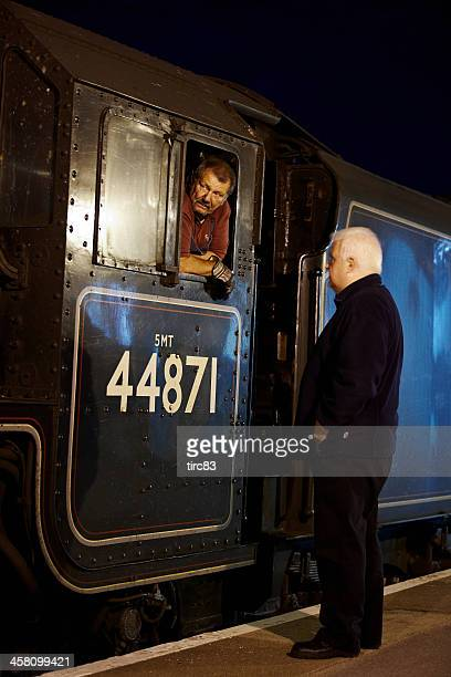Steam train driver aboard footplate at night