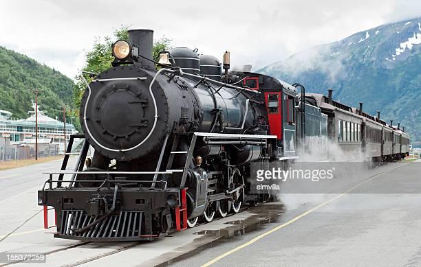 Steam train driving down tracks in Skagway, Alaska