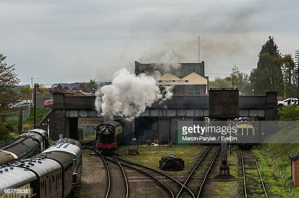 steam train emitting smoke at shunting yard against sky - loughborough stock pictures, royalty-free photos & images