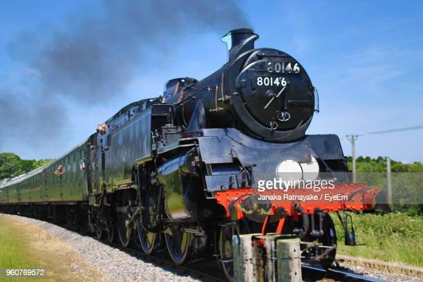 steam train on railroad track against sky - locomotive stock photos and pictures