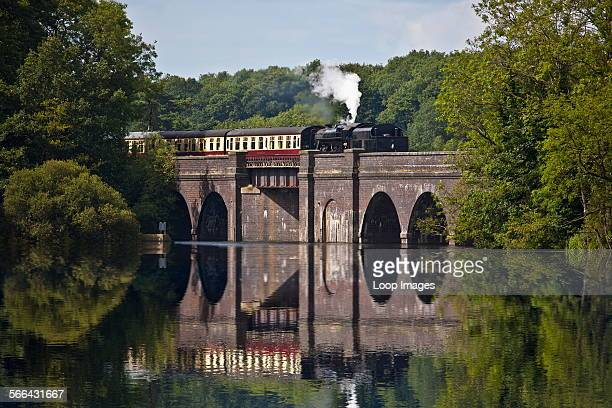 A steam train on Swithlnd Reservoir Viaduct which is part of the Great Central Railway in Leicestershire