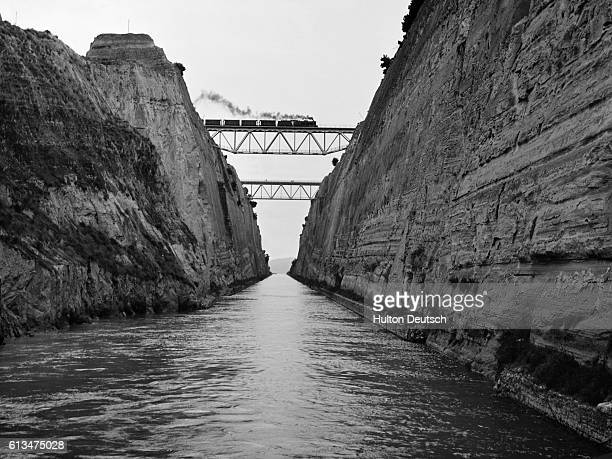 A steam train passes over the the narrow waterway which cuts across the Isthmus of Corinth | Location Isthmus of Corinth Greece