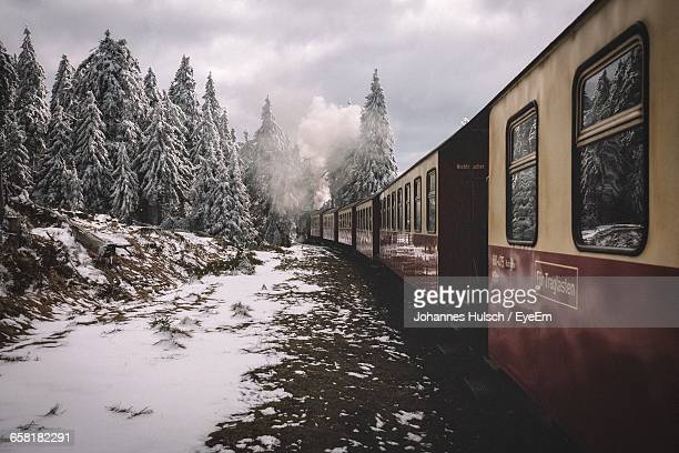 Steam Train Passing By Snow Covered Trees