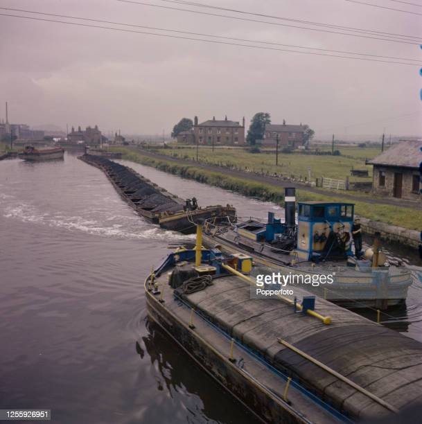 A steam tug hauls a line of tom pudding tub boats loaded with coal on the Aire and Calder Navigation between Leeds and Goole in Yorkshire England in...