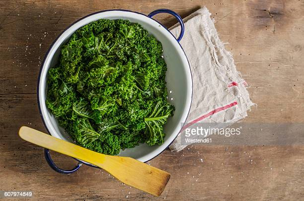 Steamed green gabbage in colander, wooden spoon