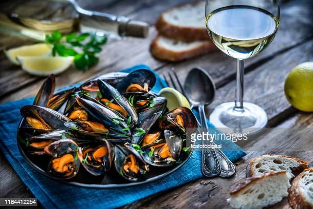 素朴な木製テーブルの上に蒸しムール貝と白ワイン - 蒸し ストックフォトと画像