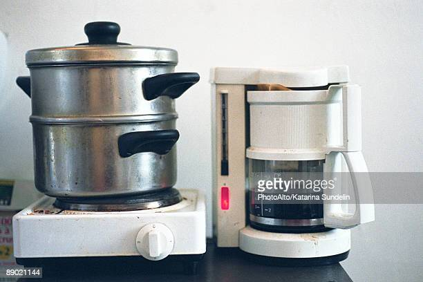 Steamer on hotplate set next to coffee maker on counter