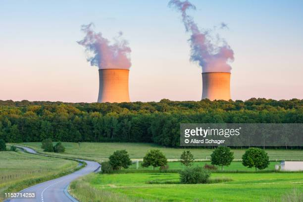 steaming cooling towers at nuclear power plant around sunset - atomic imagery photos et images de collection