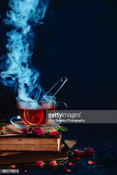 Steaming cup of tea on a stack of books. Herbal drink with rose petals. Dark food photography with copy space.
