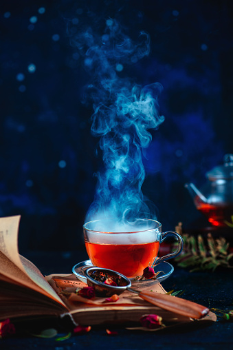 Steaming cup of tea on an open book with curly pages. Herbal drink with rose petals. Dark food photography with copy space. - gettyimageskorea