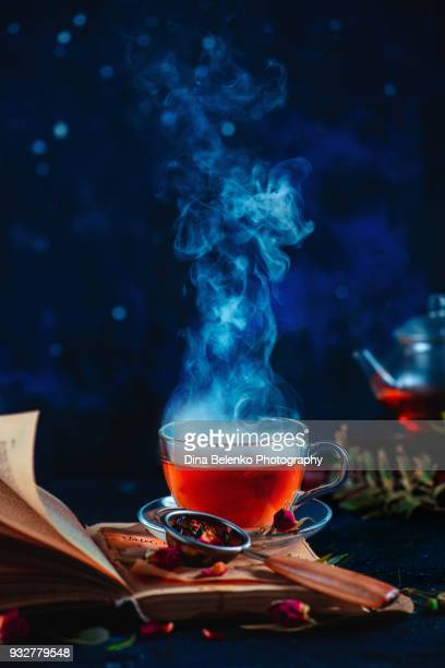 Steaming cup of tea on an open book with curly pages. Herbal drink with rose petals. Dark food photography with copy space.