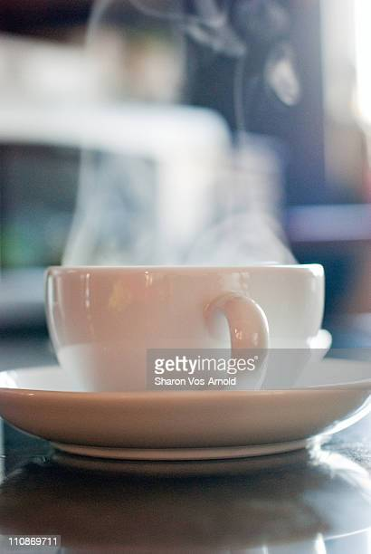 Steaming hot, white china cup of coffee