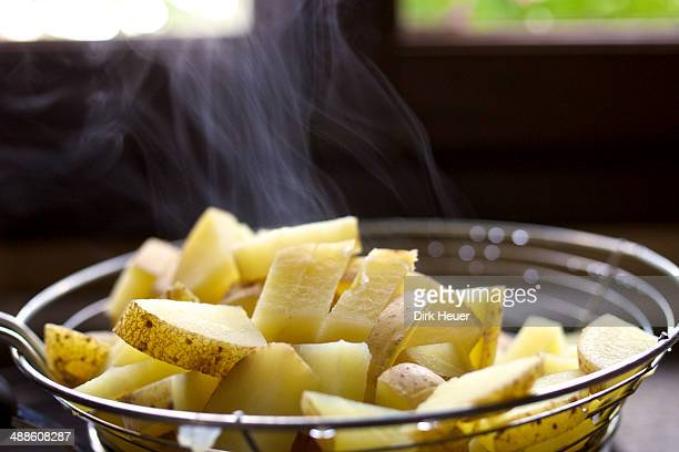 Steaming potatoes in wire sieve