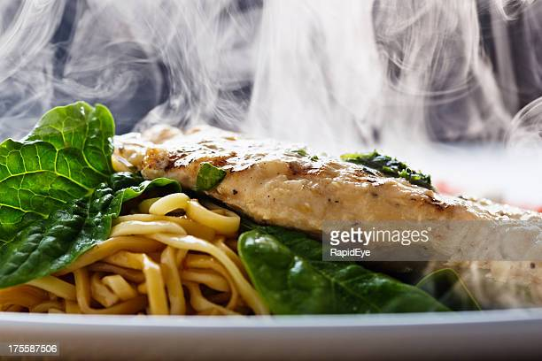 Steaming seared chicken breast with pesto, noodles and spinach