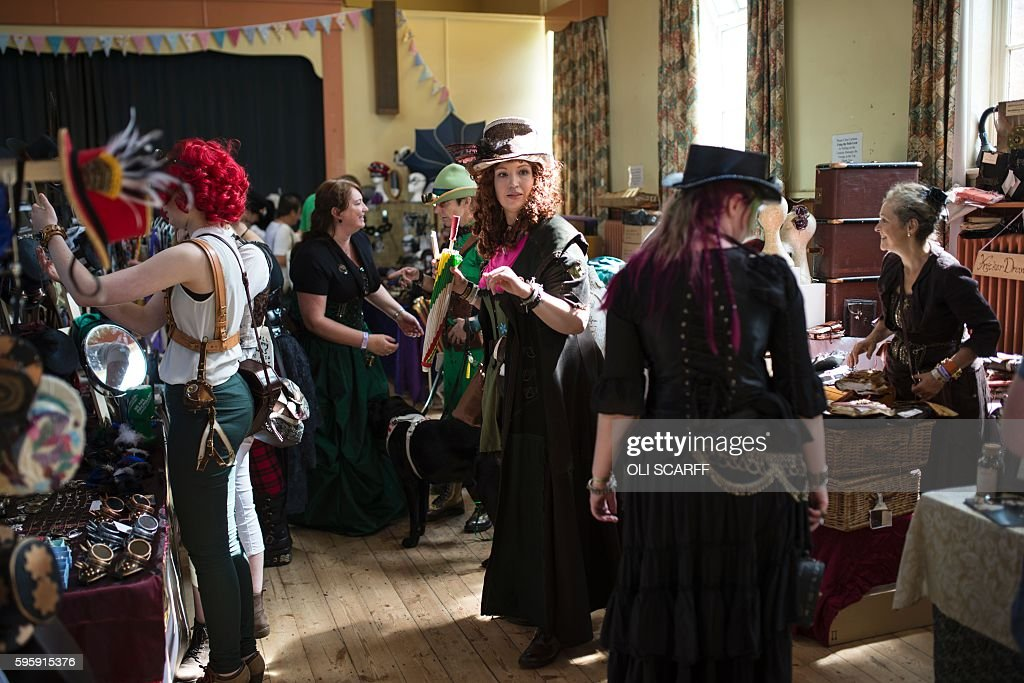 Steampunk enthusiasts attend the first day of 'The Asylum Steampunk Festival' in Lincoln, northern England on August 26, 2016. The four-day alternative lifestyle festival is the largest and longest running steampunk festival in the World; combining art, literature, music, fashion and comedy. Steampunk is a subgenre of science fiction or science fantasy that incorporates technology and aesthetic designs inspired by 19th-century industrial steam-powered machinery. / AFP / OLI