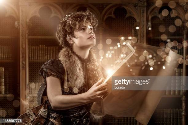 steampunk female reading a spell from a map in a library - time travel stock pictures, royalty-free photos & images