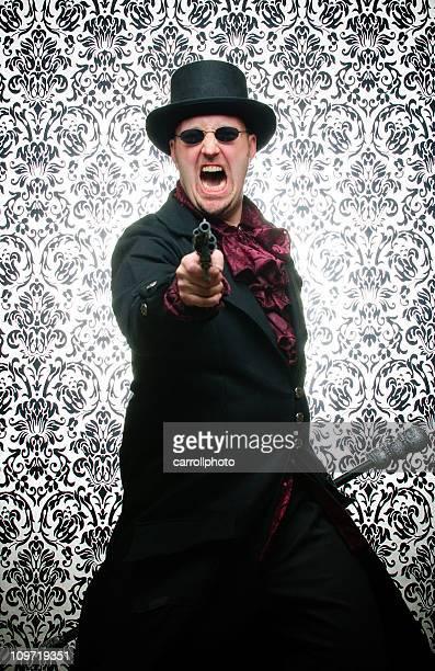 Steampunk Mann zeigt Waffe gegen Damast Hintergrund
