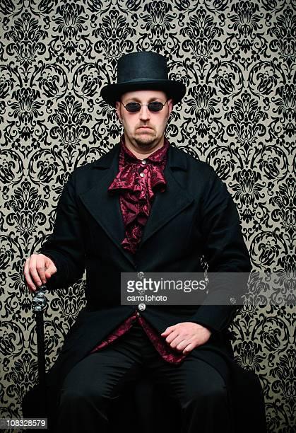 Steampunk Mann sitzt gegen Damast Hintergrund