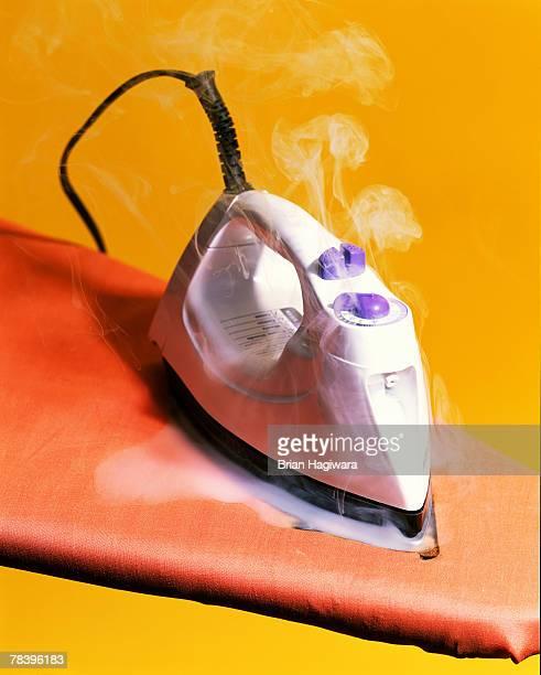 Steamy iron on ironing board