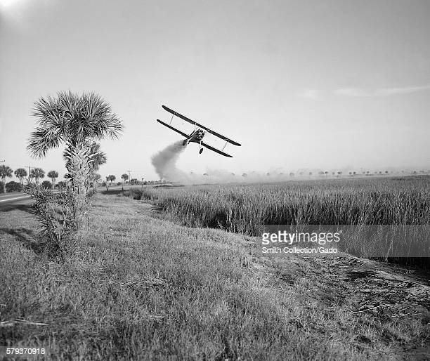 A Stearman biplane is spraying an insecticide during malaria control operations in Savannah Georgia 1973 Insecticides are important in disease...