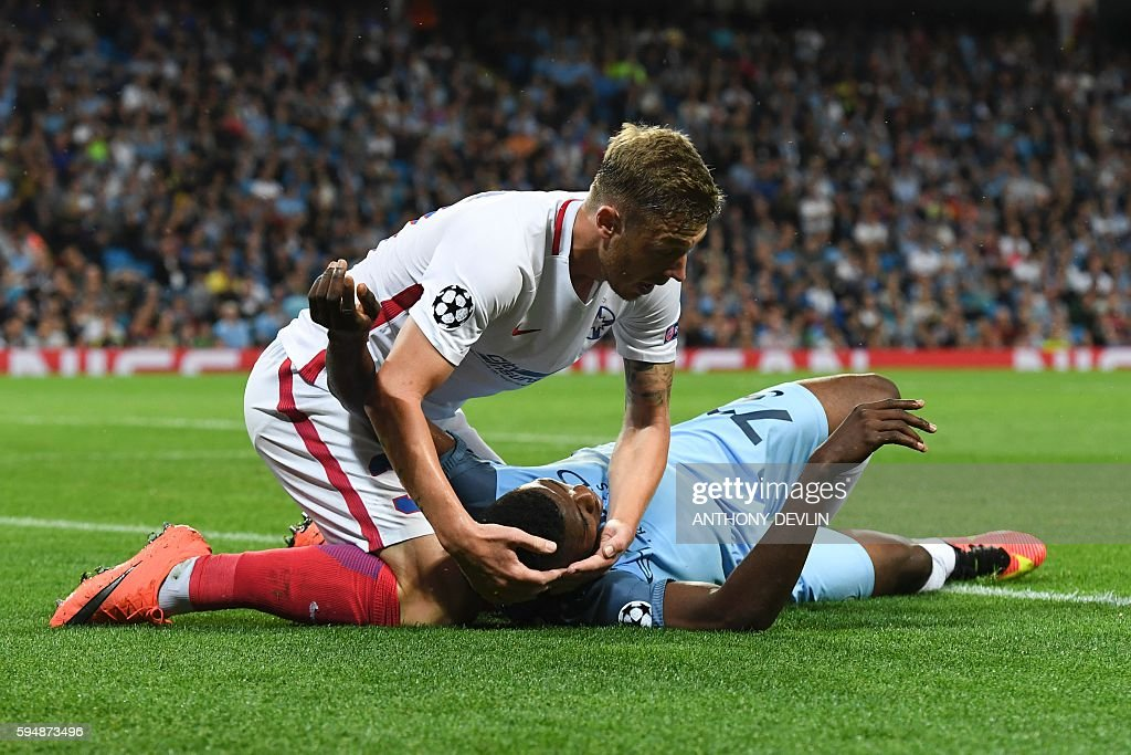 Steaua Bucharest's Romanian defender Bogdan Mitrea (L) checks on Manchester City's Nigerian striker Kelechi Iheanacho (R) who got injured during the UEFA Champions league second leg play-off football match between Manchester City and Steaua Bucharest at the Etihad Stadium in Manchester, north west England on August 24, 2016. / AFP / Anthony Devlin