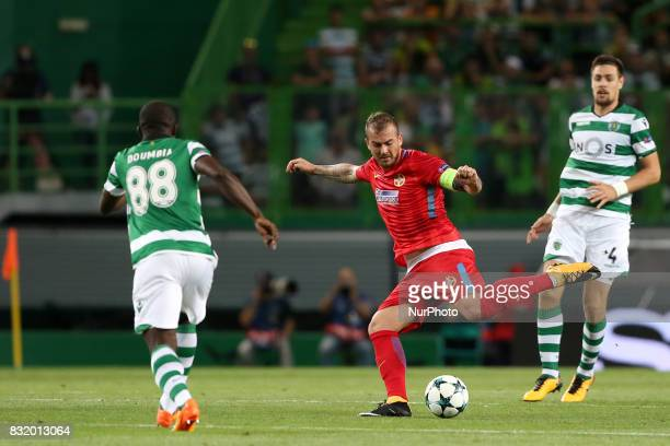 Steaua's forward Denis Alibec vies with Sporting's forward Seydou Doumbia from Ivory Coast during the UEFA Champions League playoffs first leg...