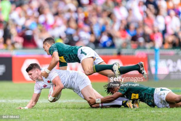 Stedman Gans and Muller du Plessis of South Africa put a tackle of Ben Howard of England during the HSBC Hong Kong Sevens 2018 match between South...