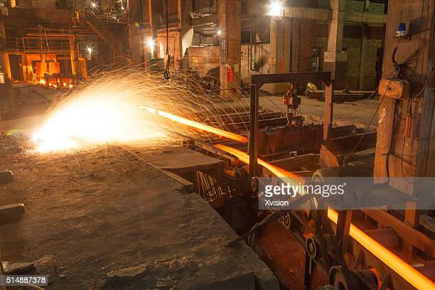 steel bar coming from the steel making furnace - fabricage apparatuur stock pictures, royalty-free photos & images