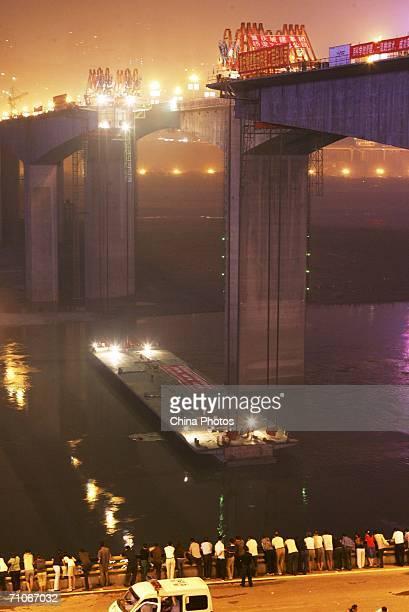 A steel box girder floats in the Yangtze River below the construction site of Shibanpo Bridge on May 26 2006 in Chongqing Municipality China The...