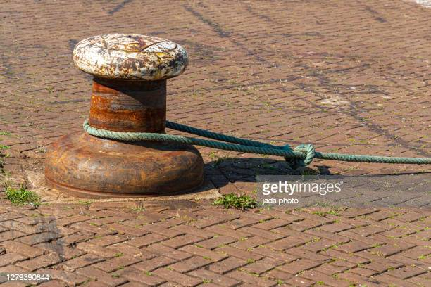steel buoy on the quay of the harbor - quayside stock-fotos und bilder