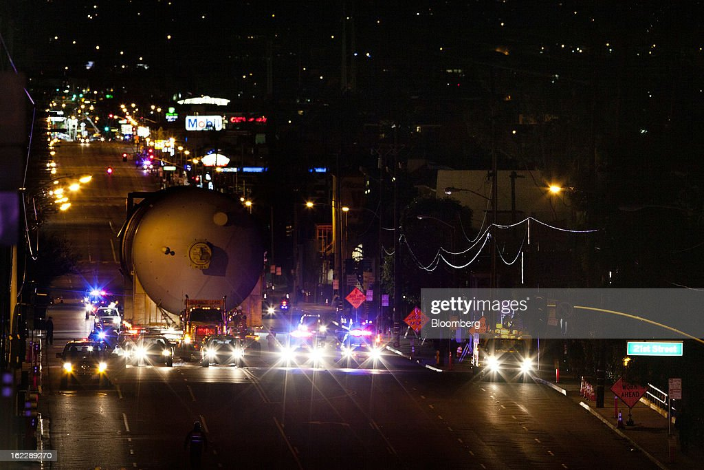 A steel coke drum is escorted by police as it is transported on a trailer manufactured by Mammoet Salvage BV along the Pacific Coast Highway in Hermosa Beach, California, U.S., on Wednesday, Feb. 20, 2013. The drum, which measures over 100 feet long and weighs over 500,000 pounds, is one of six scheduled to be delivered to Chevron Corp.'s refinery in El Segundo. Photographer: Patrick Fallon/Bloomberg via Getty Images