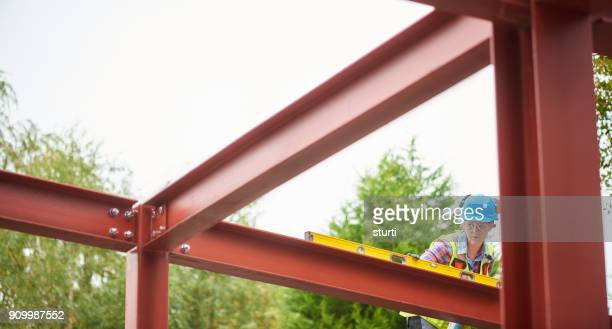 steel erector checking levels - fastening stock pictures, royalty-free photos & images