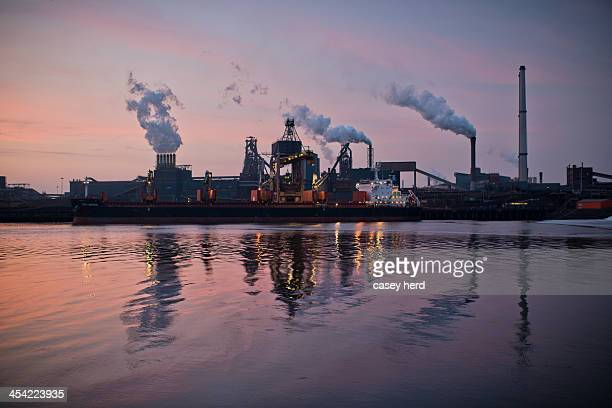 Steel factory in the port of Ijmuiden billows smoke and steam into the air and reflects off the water of the Binnen-IJ or inner IJ as the sun sets...