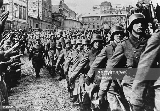 Steel helmeted German troops marching into Prague during the invasion of Czechoslovakia. By-standers are giving them a Nazi salute.