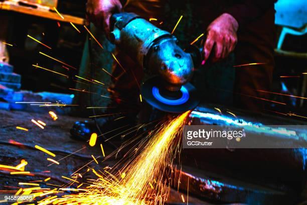 trabalhador de indústria siderúrgica moagem com cuidado a borda de metal - indústria metalúrgica - fotografias e filmes do acervo