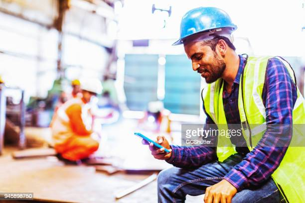 steel industry worker checking his phone - indian subcontinent ethnicity stock pictures, royalty-free photos & images