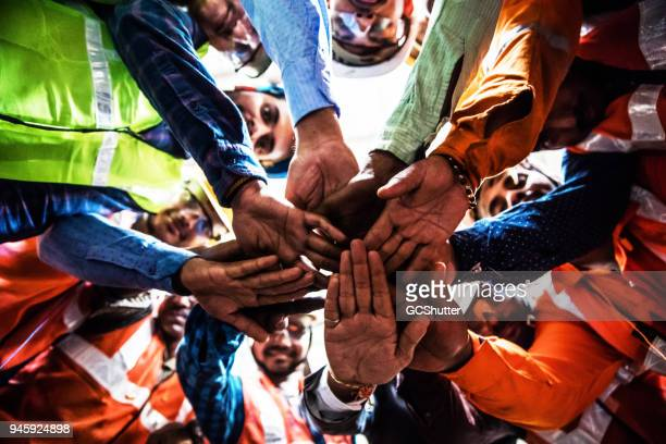 steel industry workers putting their hands together while in a circle. - stereotypically working class stock pictures, royalty-free photos & images