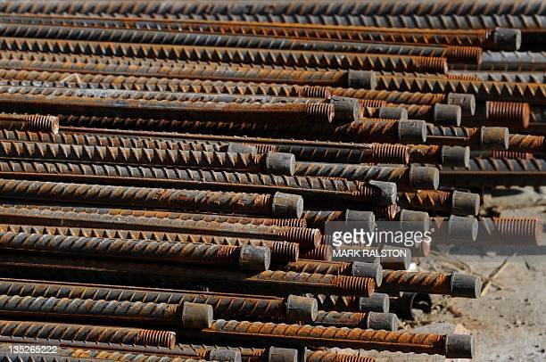 Steel rebar lies on the side of the road after being unloaded at a luxury apartments and commercial property construction site in Beijing on December...