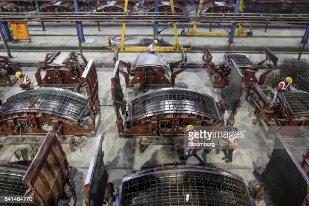 Steel reinforcing frames of precast concrete tunnel segments sit in molds at the Mumbai Metro Rail Corp casting yard in Mumbai India on Monday Aug 28...