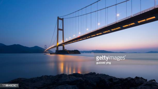 steel rope bridge across the sea in the evening - marine engineering stock pictures, royalty-free photos & images