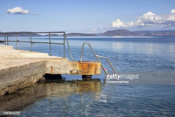 steel steps to sea at ardic on a sunny autumn day in cesme. - emreturanphoto stock pictures, royalty-free photos & images