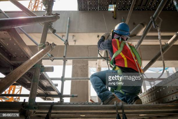 steel welding or welder industrial in the factory with smoke from welding job in construction site - safety harness stock pictures, royalty-free photos & images