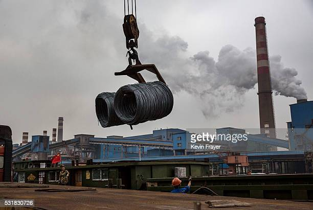Steel wire to be used in the manufacturing of tires is loaded onto a barge in the BeijingHangzhou Canal in the logistics area of the Zhong Tian Steel...