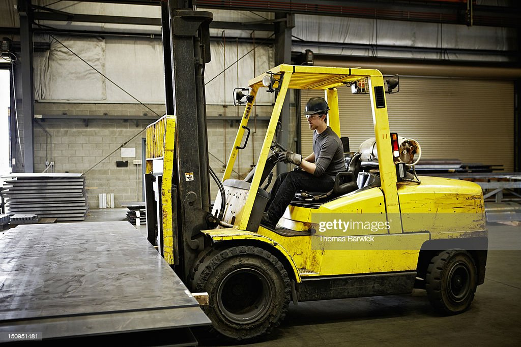 Steel worker driving forklift to move steel : Stock-Foto