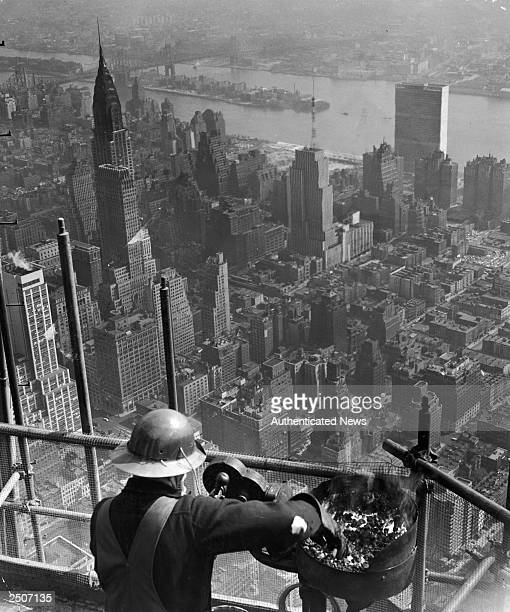 A steel worker heats iron bolts during the erection of a new television antenna on the top of the Empire State Building New York City 1940s