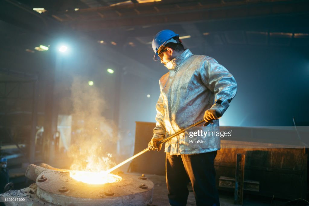 Steel worker in protective clothing raking furnace in an industry : Stock Photo
