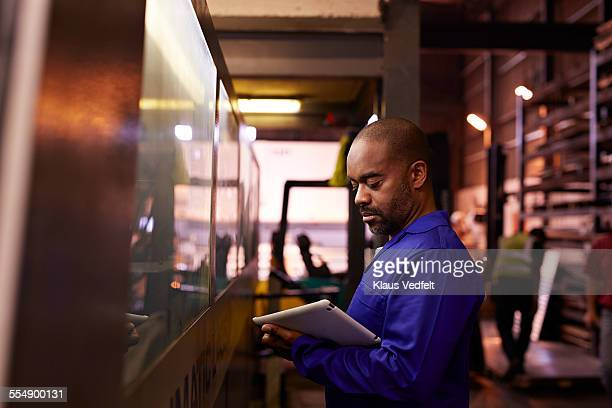 Steel worker looking at tablet next to big machine